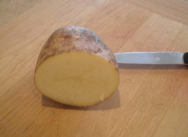 клубень картофеля разрезать пополам