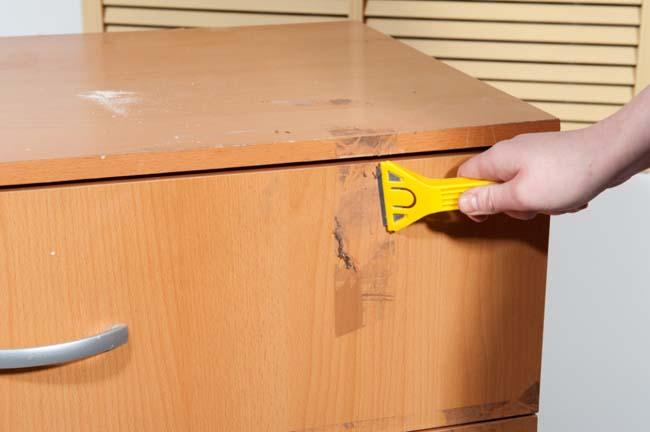 пластиковым шпателем оттираем следы двухстороннего скотча от мебели